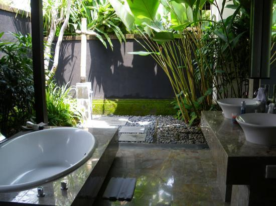 Outdoor bathtub and sinks in a grey, slate, tile and pebbled private garden