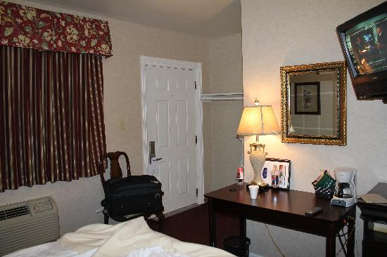 Cocca's Inns & Suites Albany Airport: TV, desk, and fridge.