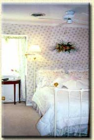 Gatehouse Bed and Breakfast: Compass Rose Room - A very special room festooned in roses, eyelet, wicker and a white-iron doub