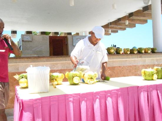 Excellence Playa Mujeres: Teaching us how to make Coco Locos by The Sol bar.