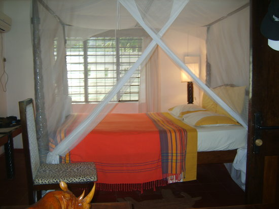 Coral Beach Cottages: OUR BED ROOMS WITH MOSQUITO NETS