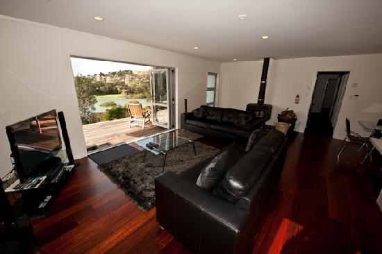 Sandspit Retreat: Our 3 Bedroom house's open plan lounge to outside Estuary /bush  views