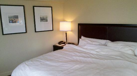 The Westin Edmonton: King size bed and side table with lamp.