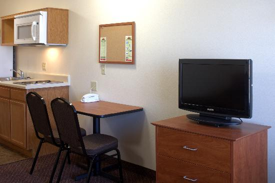 Value Place Round Rock: Interior studio - TV, desk, and kitchen area.