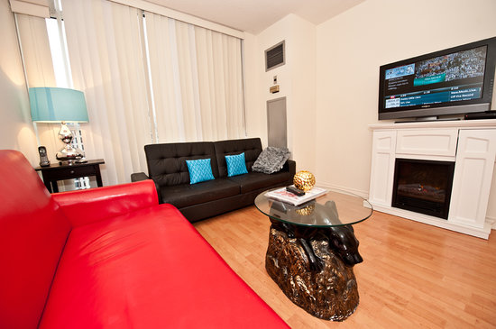 Canada Suites Toronto Furnished Rentals: 1 Bedroom Deluxe Suite - Living Room with 2 sofa beds, a Fireplace &amp; a Plasma TV