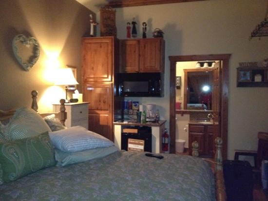 """Allseasons Treehouse Village: bed, """"kitchen area"""", looking into bathroom of cabin #5, electric fireplace to the right"""