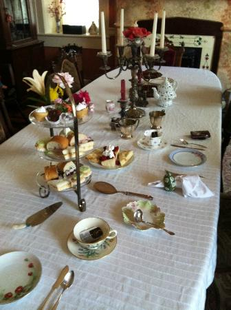 , : The dining room table set for afternoon tea.