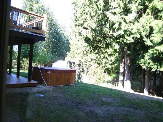 Adventurer&#39;s Guest House: View of deck and hot tub overlooking garden from dining room