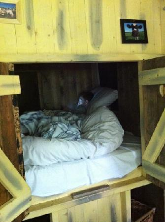 Feather Down Farms at Howbeck Lodge: my son getting comfy in his bed in the little cupboard