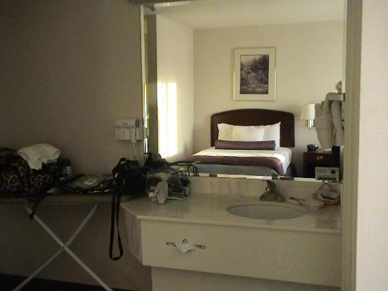 Ashmore Inn & Suites: Bathroom vanity and mirror with bed reflecting