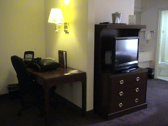 Ashmore Inn & Suites: Showing desk and television area