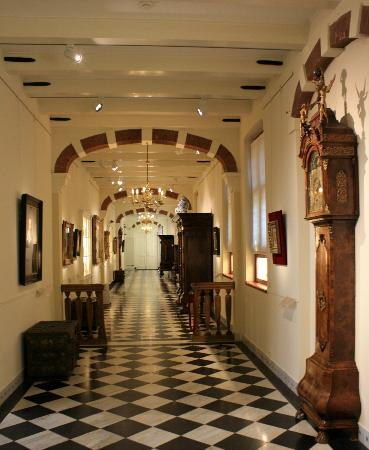 Frans Hals Museum: A hall in the museum full of paintings, furniture and clocks