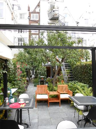Hotel Synopsis: Garden dining area looking back at rooms/kitchen area