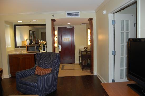 The Hotel at Auburn University: View of entrance door with powder room to left of door and bar/sink/refrigerator.