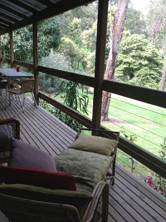 Woodbox Retreat & Studio: large deck over green garden with glimpse of mountains
