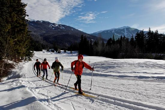 Whistler, Canada: A family cross-country skis on a trail at Lost Lake Park on a sunny day. Photo credit: Toshi Kaw
