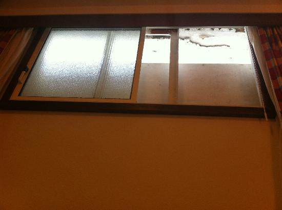 Hotel Santa Clara Evora Centro: Detail of the small cell window of the room partially cover by a a wall