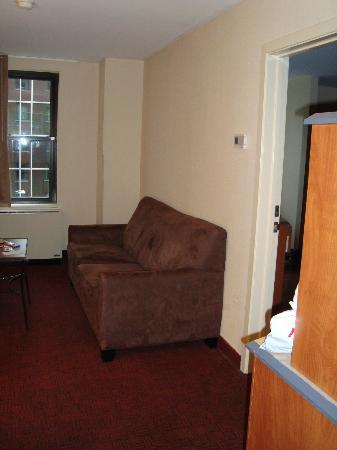 Red Roof Inn: Living room space with a hide-a-bed. Microwave and fridge stand on the right (in the wood cabine