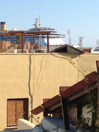 Spot Hotel: view from roof garden. A cruise ship goes by behind the building