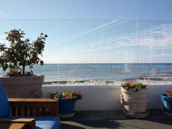 The Inn at Sunset Cliffs: View behind the windscreen on the upper terrace, with the hotel in the reflection.