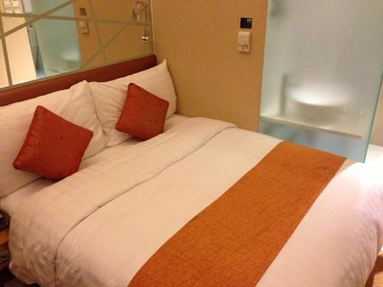 Dorsett Mongkok Hong Kong: Soft fluffy pillows with mirror behind, frosted glass to the toilet