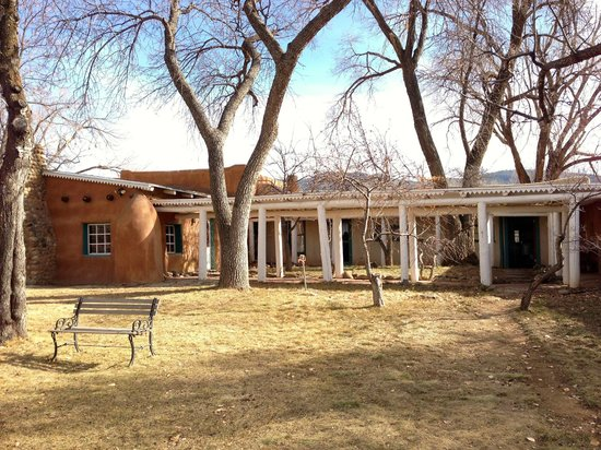 Mabel Dodge Luhan House: The Log Cabin and more guest rooms behind the collonade.