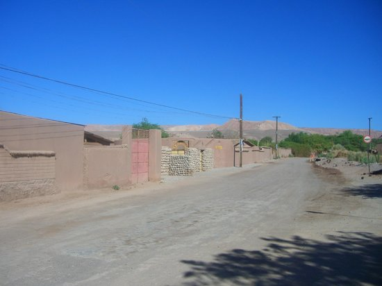 Altiplanico Atacama: the dusty road and not very exciting entrance behind the stones [ not the iron gate].