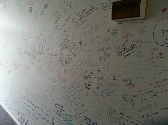 Adventure Queenstown Hostel: Wall that is filled up by all the guests that have stayed in AQ