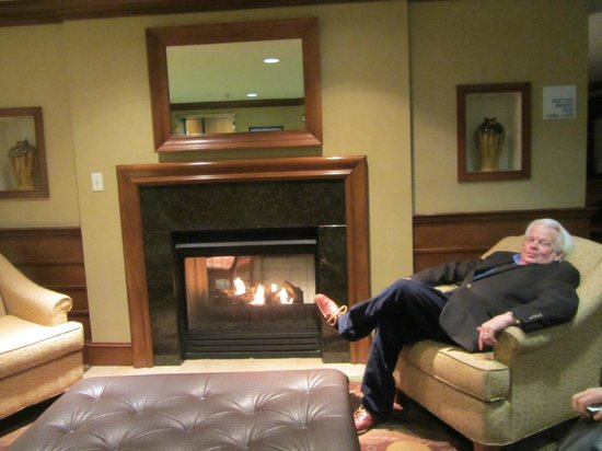Holiday Inn Express Chapel Hill: My husband enjoying the wonderful fireplace in the lobby!  It also opens into the breakfast room