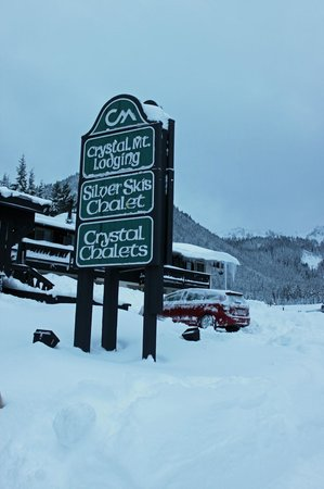 Crystal Mountain Lodging Suites:                   Crystal Mt Lodging Sign with Silver Ski Chalet in Background
