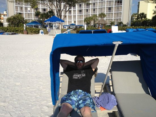 Guy Harvey Outpost, a TradeWinds Beach Resort:                   the hubby relaxing in a cabana with the hotel behind him
