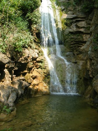 Haryana, Indien:                   Waterfall above the lake