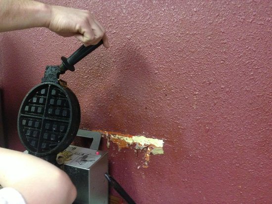 Comfort Inn: The damaged wall with peeling paint by the waffle iron