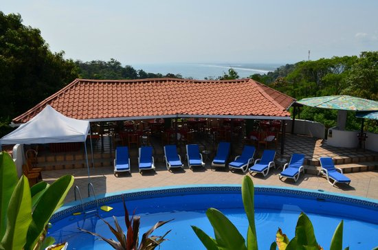 Hotel California: comedor junto a piscina con vista al mar y bosque
