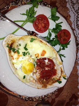 Antebellum Guest House : egg dish with tomatoes and topped with cheese . Served piping hot