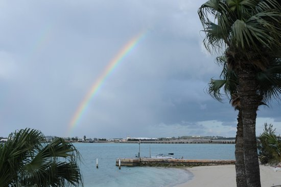 Grotto Bay Beach Resort: Rainbow over Bailey's Bay, from pool area.