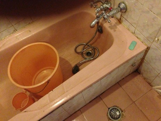 Hotel Darshan: unclean and age-old bath tub with a broken shower and a hot water mixer