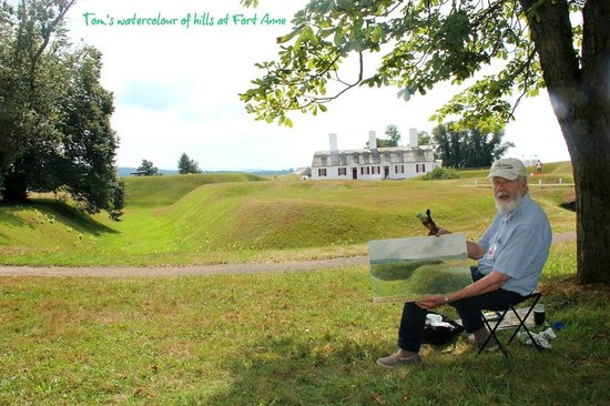 -, : An artist paints the dramatic hills of Fort Anne National Park