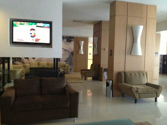 Staybridge Suites Guadalajara Expo : Sala de estar con TV y libros 