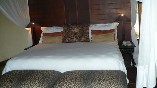 Shishangeni Lodge: the bedroom with 4 postr bed and mosquiti curtains.
