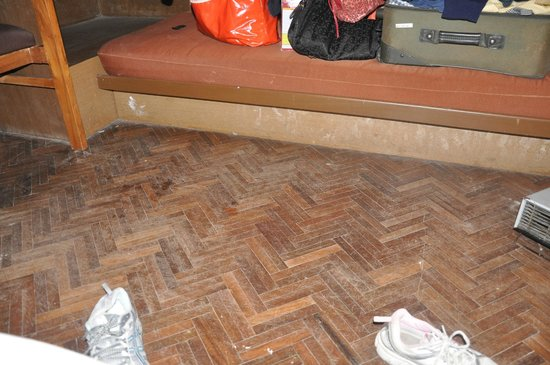 Sinclairs Darjeeling: dirty scratched room floor and dilapidated sitting area