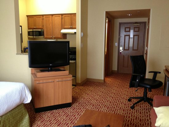 TownePlace Suites Cleveland Airport: View with bed are to left, seating are to right with kitchen behind TV
