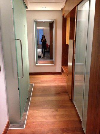 Le Meridien Barcelona: hallway with mirror near entryway, flanked by bathroom on the left, closet on the right