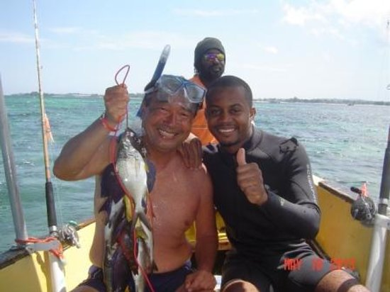 ClubHotel Riu Negril: Romeo wearing snorkeling equipment with a local diver holding catch for the day