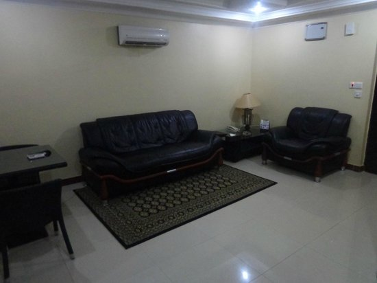 couch in the suite with airconditioner above picture of