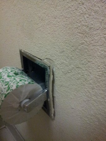 Knights Inn San Antonio Near AT&T Center: paper towel holder with chipped paint, rust and falling apart.