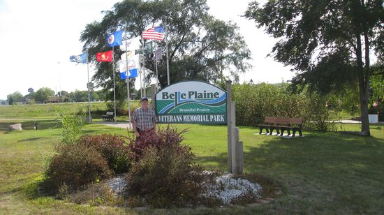 Belle Plaine Veterans Memorial Park: Park sign with the plaza of service flags in the background