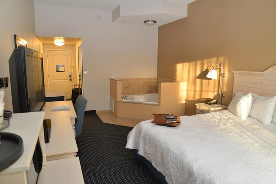 Hampton Inn and Suites Cape Cod - West Yarmouth: king bed w/ hot tub. microwave&fridge in left foreground.