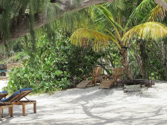 Guana Island: Beach area with lounge chairs, a cannon, and a hammock