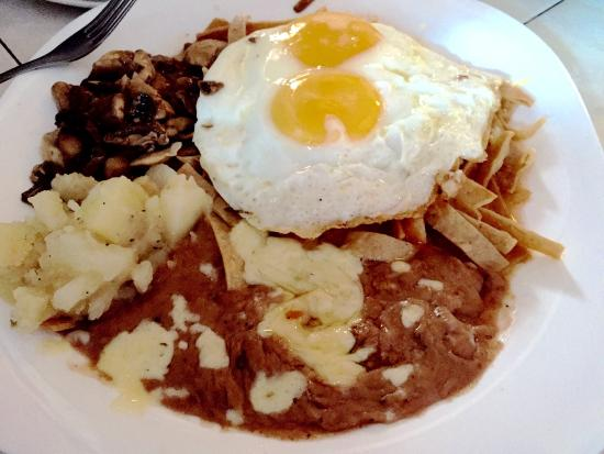 Chilaquiles with fried eggs and refried beans. Potatoes and a side of ...